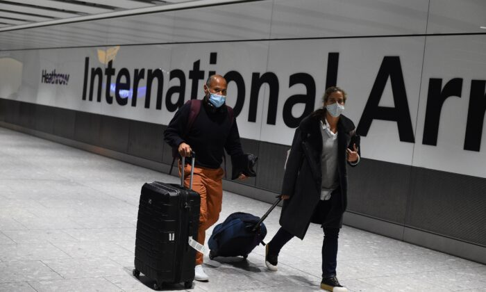 Passengers walk with luggage through the Arrival Hall of Terminal 5 at London's Heathrow Airport on Jan. 18, 2021. (Kirsty O'Connor/PA)