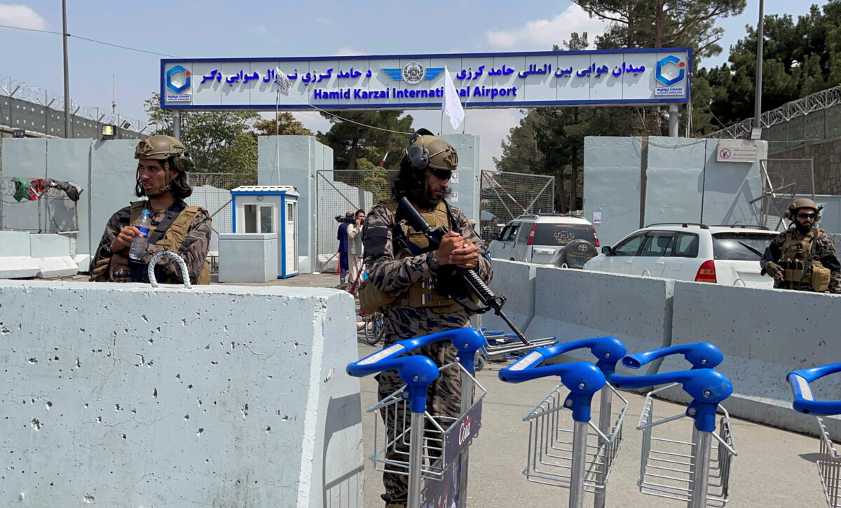 Taliban forces stand guard at the entrance gate of Hamid Karzai International Airport a day after U.S troops withdrawal in Kabul