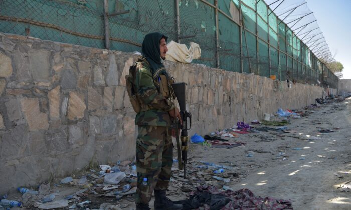 A Taliban fighter stands guard at the site of the Aug. 26 twin suicide bombs, which killed scores of people including 13 U.S. troops, at Kabul airport in Afghanistan on Aug. 27, 2021. (Wakil Kohsar/AFP via Getty Images)