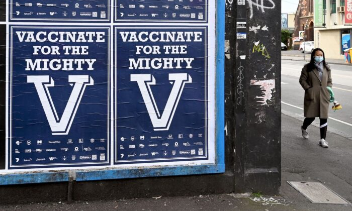 A person walks past posters encouraging people to get vaccinated in Melbourne, Australia, on Aug. 31, 2021(William West/AFP via Getty Images)