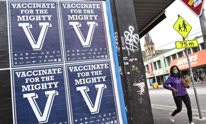 A person walks past posters encouraging people to get vaccinated in Melbourne, Australia on Aug. 31, 2021. (William West/AFP via Getty Images)