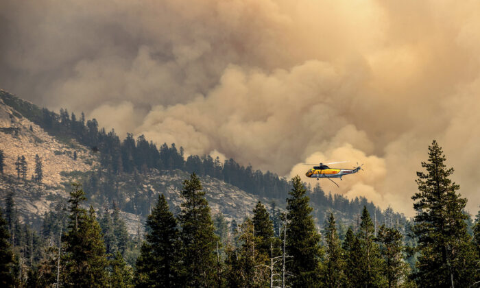 A helicopter flies over Wrights Lake while battling the Caldor Fire in Eldorado National Forest, Calif., on Sept. 1, 2021. (AP Photo/Noah Berger)