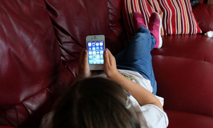 A child uses an Apple smartphone in this undated file image. (PA)
