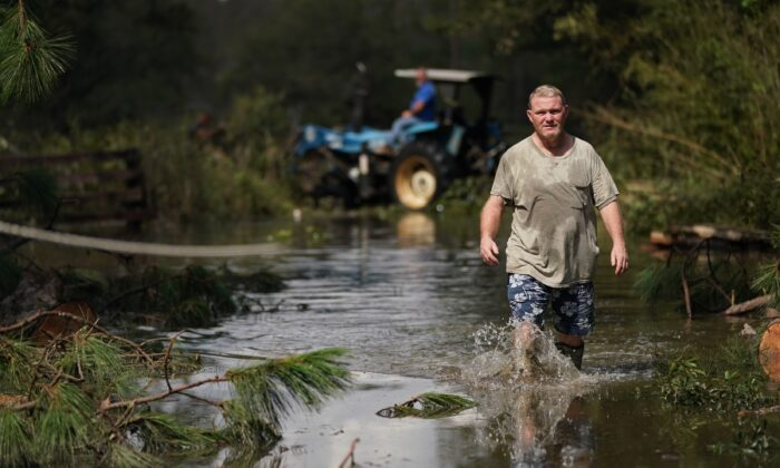 Russell Threeton, a strawberry farmer, walks through floodwater after Hurricane Ida in Springfield, La., on Sept. 1, 2021. (Sean Rayford/Getty Images)