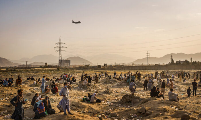 A military transport plane launches off while Afghans left behind watch in Kabul, Afghanistan, on Aug. 23, 2021. (Marcus Yam/Los Angeles Times/TNS)