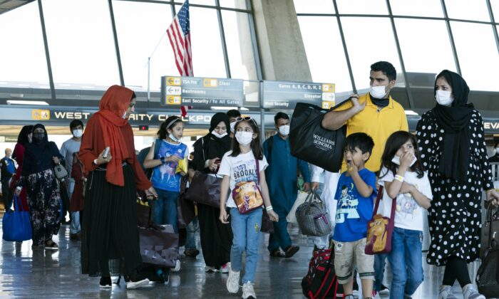 Families evacuated from Kabul, Afghanistan, walk through the terminal before boarding a bus after they arrived at Washington Dulles International Airport, in Chantilly, Va., on Sept. 2, 2021. (Jose Luis Magana/AP Photo)