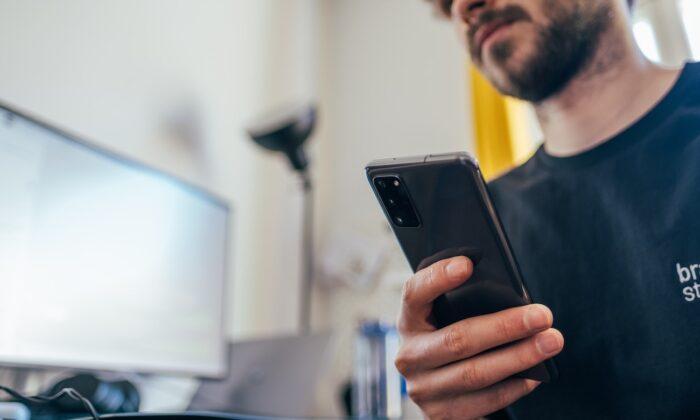 Man holding a phone while indoors. (Jonas Leupe/Unsplash)
