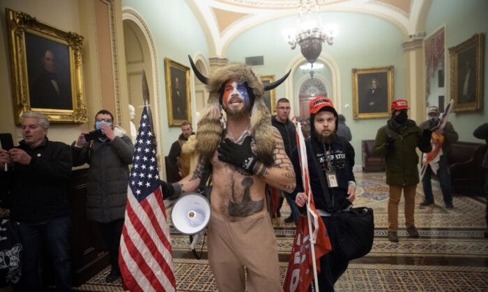 """The accused U.S. Capitol rioter dubbed the """"QAnon Shaman,"""" Jacob Chansley (center) and other protestors outside the Senate chamber of the U.S. Capitol Building in Washington on Jan. 6, 2021. (Win McNamee/Getty Images)"""