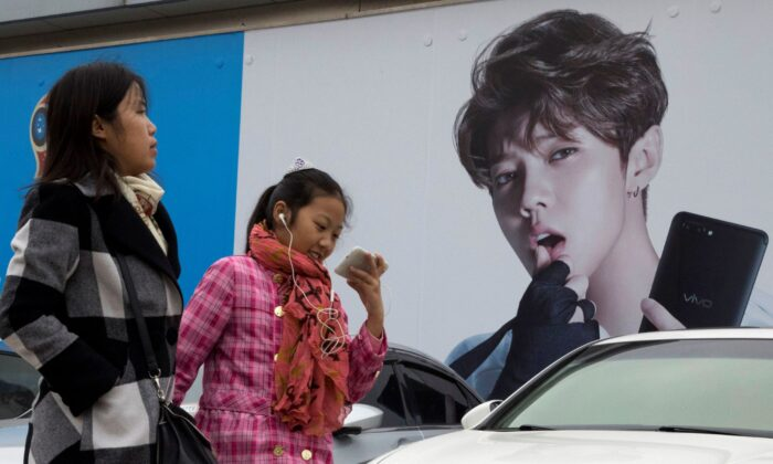 Chinese women walk past advertisement featuring teen idol Lu Han, also known as China's Justin Bieber in Beijing, China, on Oct. 21, 2017. (Ng Han Guan/AP Photo)