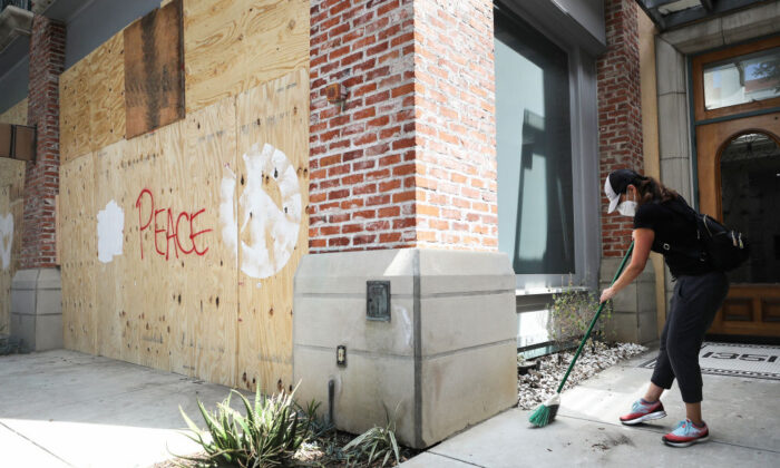 A volunteer cleans in front of a shop window boarded up a day after looting occurred amid protests in Santa Monica, Calif., on June 1, 2020. (Mario Tama/Getty Images)