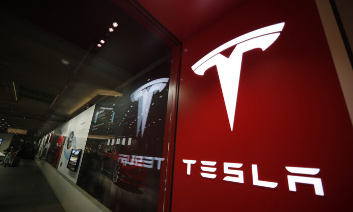 A file photo of a sign bearing the company logo outside a Tesla store in Cherry Creek Mall in Denver. (David Zalubowski, File/AP Photo)