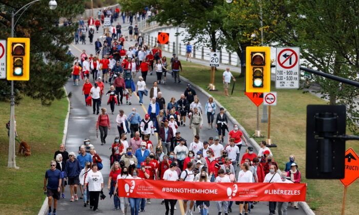 Supporters of Michael Kovrig and Michael Spavor march to mark 1,000 days since the Canadians were arrested in China, during a protest in Ottawa on Sept. 5, 2021.  (Reuters/Blair Gable)