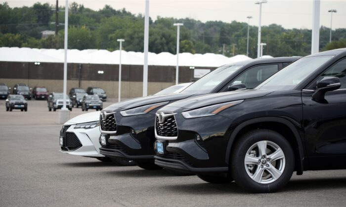 A pair of unsold 2021 Highlander sports utility vehicles and a Camry sedan are parked on the empty storage lot outside a Toyota dealership in Englewood, Colo., on Aug. 29, 2021. (David Zalubowski/AP Photo, File)