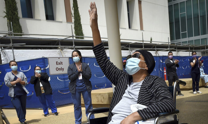 Karen Parker-Bryant, 64, raises a hand skyward after she was released from Clovis Community Hospital after a battle with COVID-19, in Fresno, Calif., on May 19, 2020. (John Walker/The Fresno Bee via AP, File)