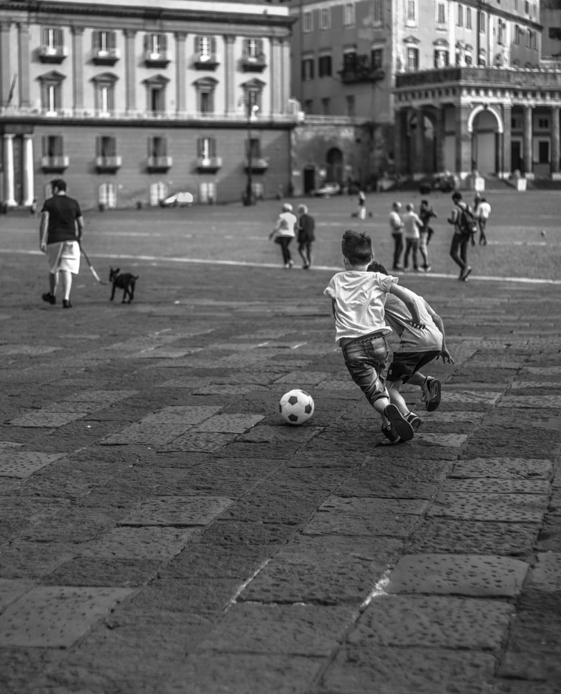 Kids,Playing,Soccer,In,A,Square,Of,Napoli,-,Italy