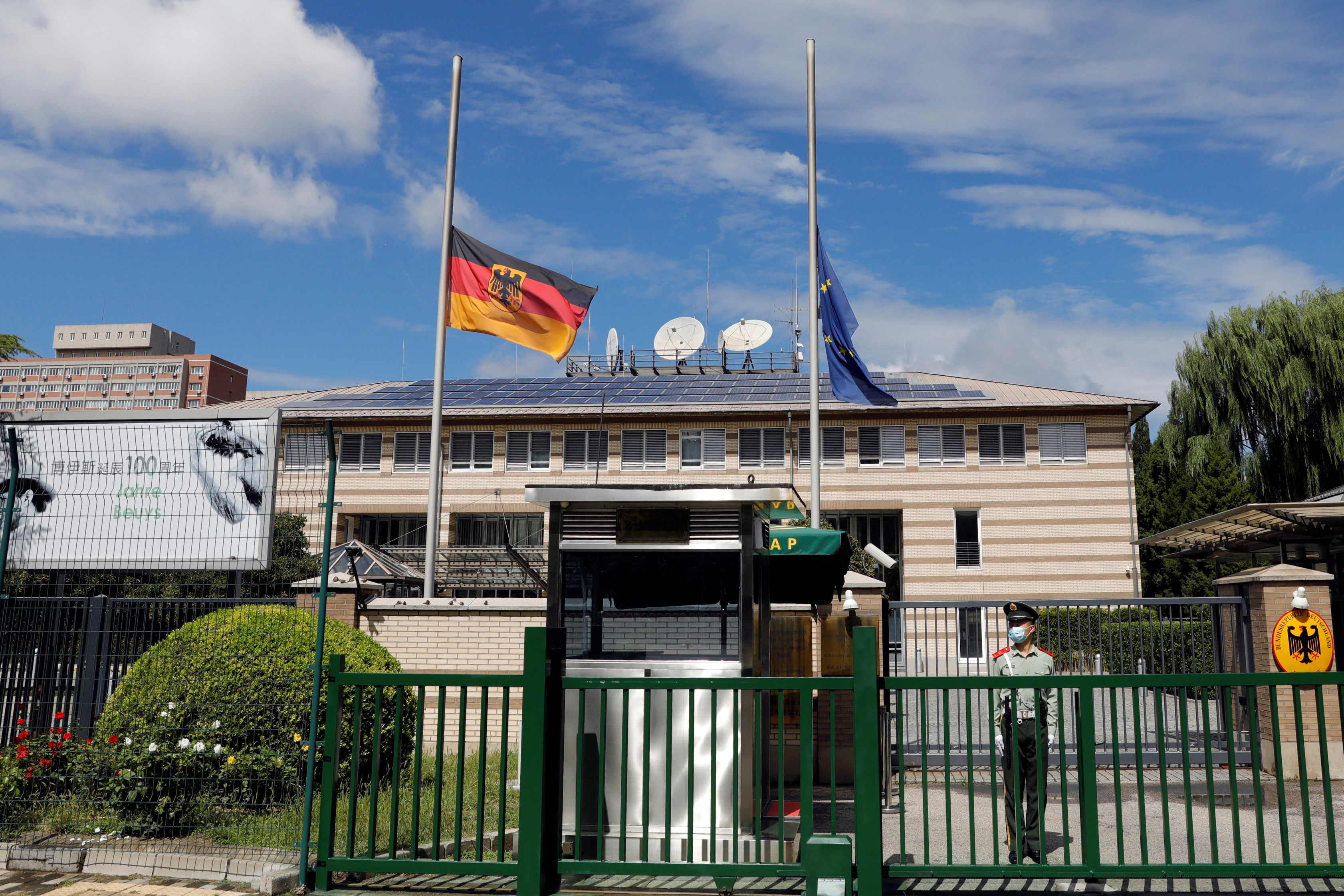 German and European Union flags fly at half mast at the Germany embassy in Beijing