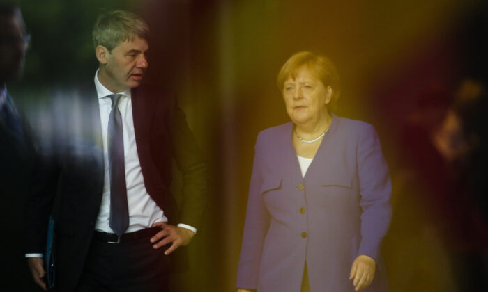 German Chancellor Angela Merkel (R), talks to then foreign policy advisor Jan Hecker (L), as she arrives to welcome the Prime Minister of North Macedonia Zoran Zaev for a meeting at the chancellery in Berlin on June 13, 2019. (AP Photo/Markus Schreiber, File)