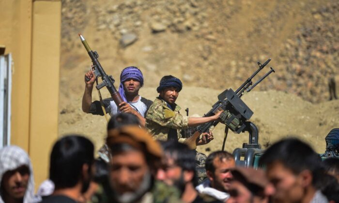 Afghan resistance movement and anti-Taliban forces stand on the back of a pickup truck as they gather in Abshar district, Panjshir Province, on Aug. 28, 2021. (Ahmad Sahel Arman/AFP via Getty Images)