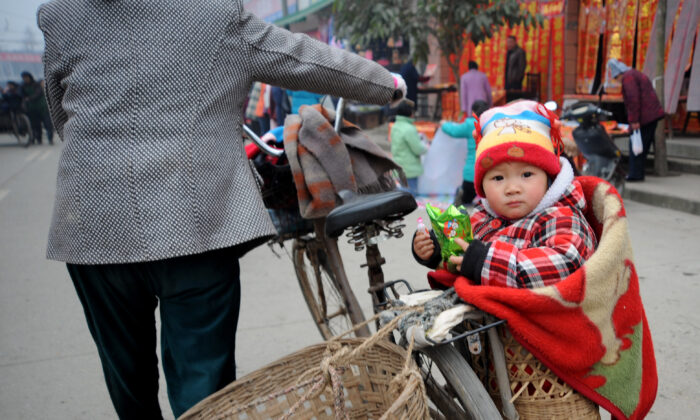 A baby sits in a basket on his way home after shopping for spring festival couplets in Chengdu of Sichuan Province, China, on Jan. 16, 2009. (China Photos/Getty Images)