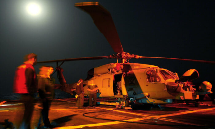 Personnel work on a Seahawk helicopter as a full moon rises behind them on the flight deck of the USS San Jacinto on March 18, 2003. (Mark Wilson/Getty Images)