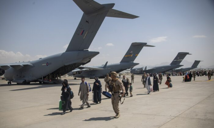 UK armed forces lead Afghan evacuees to a plane at Kabul airport, Afghanistan, in an undated file photo. (LPhot Ben Shread/MoD/PA)