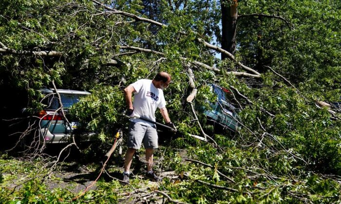 Larry Ackley is helping to clear a fallen tree in a church member's house in Fort Washington, Pennsylvania on September 2, 2021, following the aftermath of heavy rains and strong winds from the wreckage of hurricane Ida that struck the area. ..  (AP Photo / Matt Rourke)