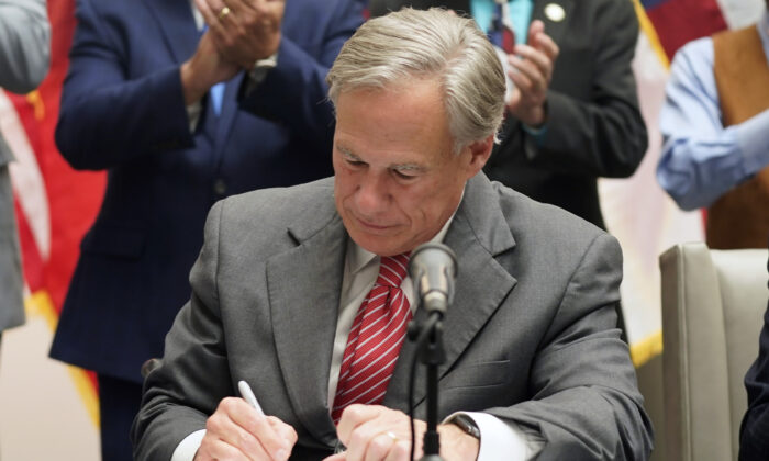 Texas Gov Greg Abbott signs Senate Bill 1, also known as the election integrity bill, into law in Tyler, Texas, on Sept. 7, 2021. (LM Otero/AP Photo)