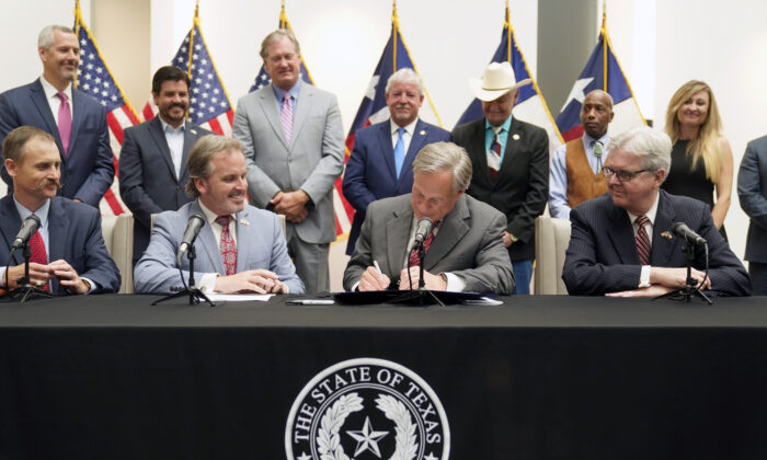 Texas Gov Greg Abbott signs Senate Bill 1, also known as the election integrity bill, into law with State Sen. Bryan Hughes ( R-Mineola), front center left, Andrew Murr (R-Junction),  front left, and Lieutenant Governor Dan Patrick, front right, looking on with others in the back ground in Tyler, Texas, on Sept. 7, 2021. (LM Otero/AP Photo)