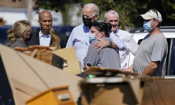 President Joe Biden hugs a woman as Sen. Cory Booker (D-N.J.) (2nd L), New Jersey Gov. Phil Murphy, (2nd R), and others look on as officials tour a neighborhood impacted by Hurricane Ida in Manville, N.J., on Sept. 7, 2021. (Evan Vucci/AP Photo)