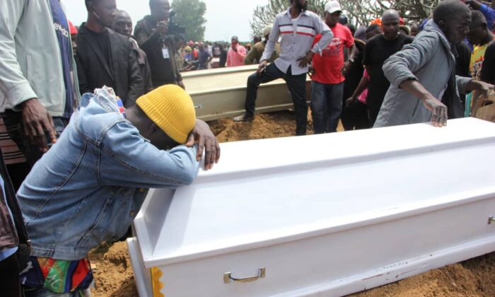 A boy weeps on a coffin at a mass funeral at Yelwan Zangam, Nigeria, on Aug. 28, 2021. (Masara Kim/The Epoch Times)