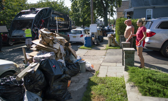 Residents wait a worker picking up debris in Passaic, NJ., from their flood damaged home in the aftermath of Hurricane Ida, on Sept. 6, 2021. (AP Photo/Eduardo Munoz Alvarez)