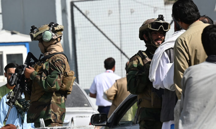 Taliban terrorists stand guard at a checkpoint as airport workers queue to enter to the Kabul International Airport in Kabul on Sept. 4, 2021. (Aamir Qureshi/AFP via Getty Images)