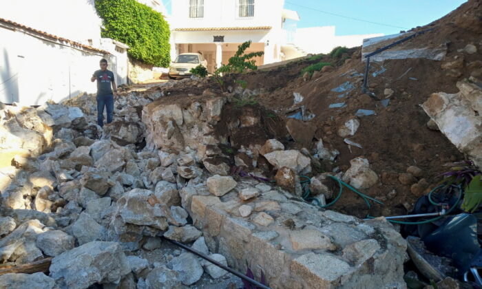 A man shows a wall that collapsed due to a landslide as a series of strong aftershocks rippled through the city after a powerful earthquake in Acapulco, Mexico, on Sept. 8, 2021. (Uriel Sanchez/Reuters)