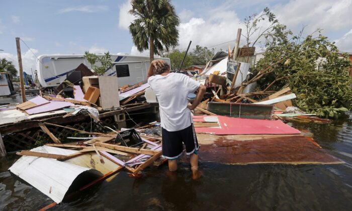 Larry Dimas is investigating the wreckage of a trailer rented to others in the aftermath of Hurricane Irma on September 11, 2017 in Immokalee, Florida.  (AP Photo / Gerald Herbert)
