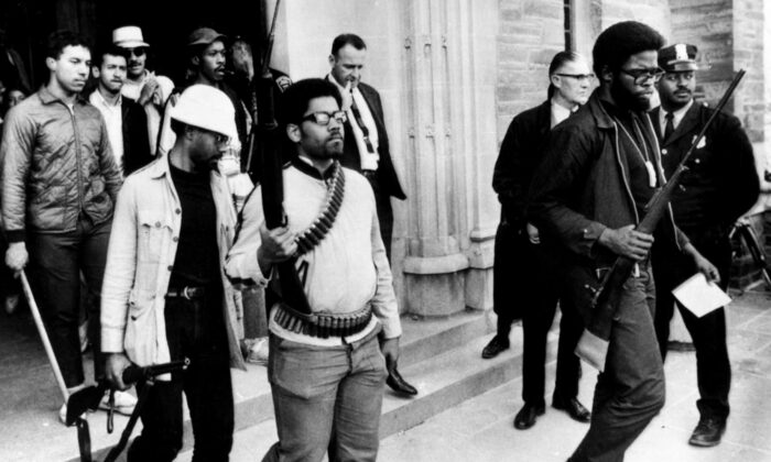 """""""Campus Guns"""", a photograph of armed black student activists leaving Willard Straight Hall at Cornell University after having occupied it for 36 hours in April 1969 in protest of racism at the university. (Public Domain)"""
