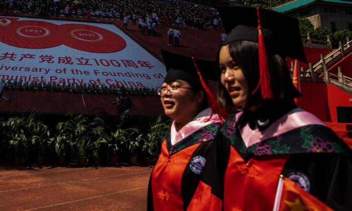 Two graduates pass by a big screen showing the centenary of the CCP at Wuhan University in Wuhan, China, on June 23, 2021. (Getty Images)