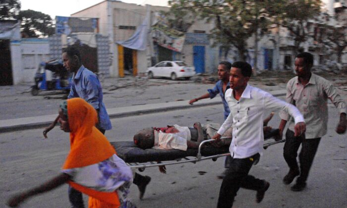 People carry a victim of a terror attack at the Ambassador Hotel, after Somalia's Al-Qaeda-linked Shabaab launched a deadly attack in Mogadishu, Somalia, on June 1, 2016. (Mohamed Abdiwahab /AFP via Getty Images)