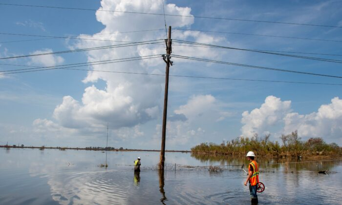Utility crews stand in water as they work on repairing power lines along Highway 23 in Plaquemines Parish, La., over a week after Hurricane Ida, on Sept. 7, 2021. (Chris Granger/The Times-Picayune/The New Orleans Advocate via AP)