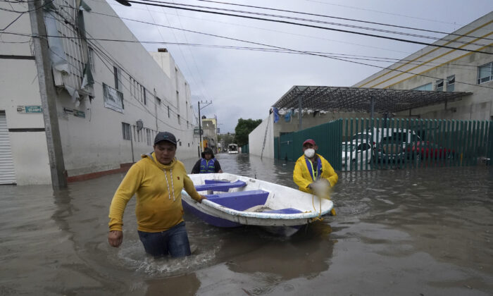 Rescuers carry inflatable boat out of a flooded hospital in Tula, Hidalgo state, Mexico, on Sept. 7, 2021. (Marco Ugarte/AP Photo)