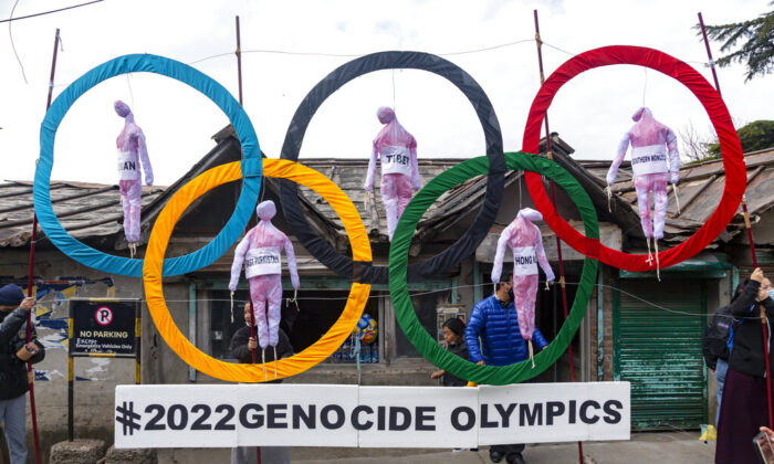 Exile Tibetans use the Olympic Rings as a prop as they hold a street protest against the holding of 2022 Winter Olympics in Beijing, in Dharmsala, India, on  Feb. 3, 2021. (Ashwini Bhatia/AP Photo)