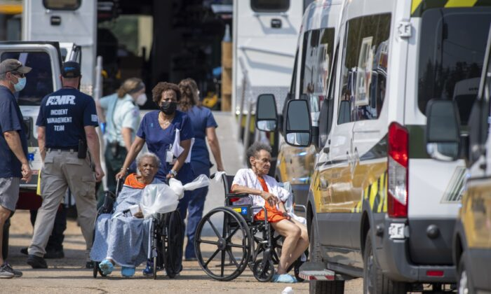 Paramedics evacuate people at a mass shelter in Independence, La., on Sept. 2, 2021. (Chris Granger/The Times-Picayune/The New Orleans Advocate via AP)
