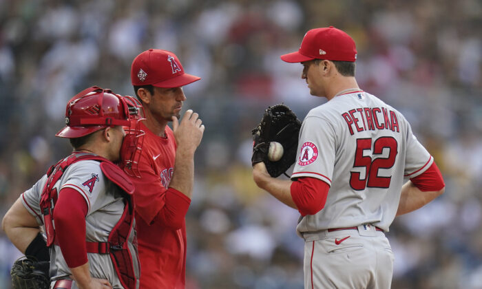 Los Angeles Angels relief pitcher Jake Petricka (52) talks with pitching coach Matt Wise, center, as catcher Max Stassi looks on during the second inning of a baseball game against the San Diego Padres in San Diego, Calif., on Sept. 8, 2021. (AP Photo/Gregory Bull)