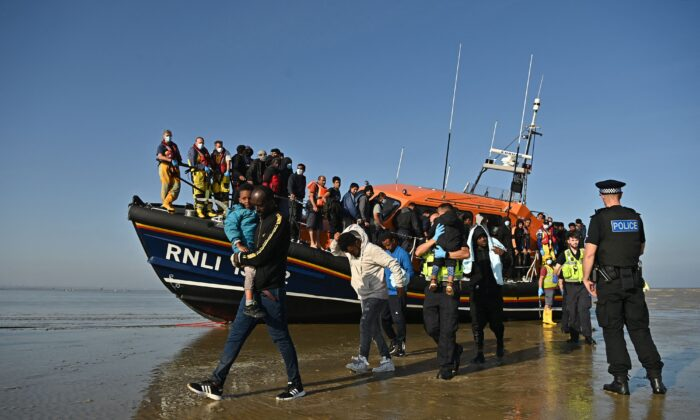 Illegal imigrants carry children as they are escorted to be processed after being picked up by an Royal National Lifeboat Institution lifeboat while crossing the English Channel at a beach in Dungeness, southeast England, on Sept. 7, 2021. (Ben Stansall/AFP via Getty Images)