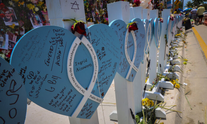 Wooden hearts with the names of victims are erected alongside the photos, flowers and other memorial items for victims of the Champlain Towers South collapse in Surfside, Fla., in a file photo. (Carl Juste/Miami Herald/TNS)