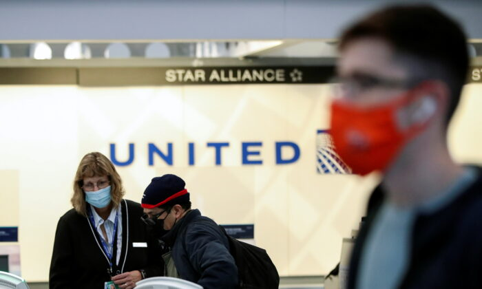 A United Airlines agent helps a customer check in for his flight at O'Hare International Airport in Chicago on Nov. 25, 2020. (Kamil Krzaczynski/Reuters)