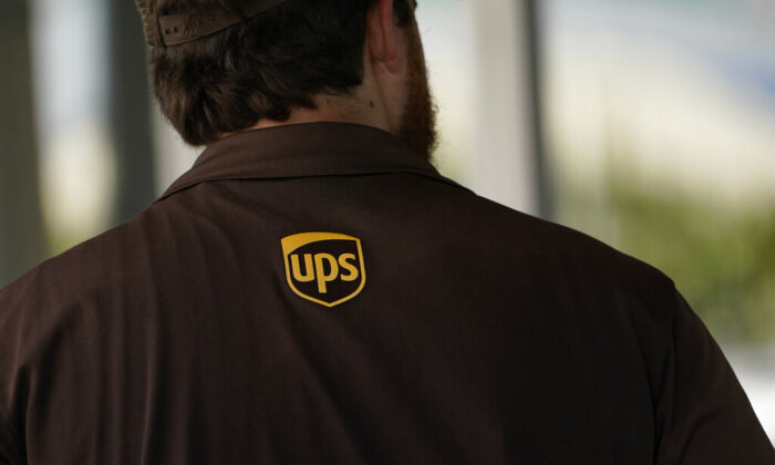 A UPS logo is on the shirt of a driver as he enters a United Parcel Service store with packages in Jackson, Miss., on July 26, 2021. (Rogelio V. Solis/AP Photo)