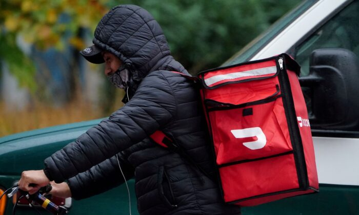 A delivery person for Doordash rides his bike in the rain during the COVID-19 pandemic in the Manhattan borough of New York City, N.Y., on Nov. 13, 2020. (Carlo Allegri/Reuters)