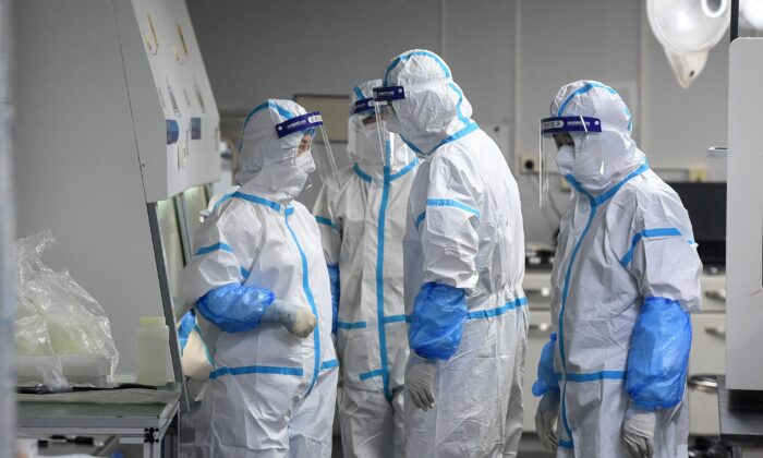 Laboratory technicians wearing personal protective equipment (PPE) work on samples to be tested for COVID-19 at the Fire Eye laboratory, a COVID-19 testing facility, in Wuhan in China's central Hubei Province, on Aug. 4, 2021. (STR/AFP via Getty Images)