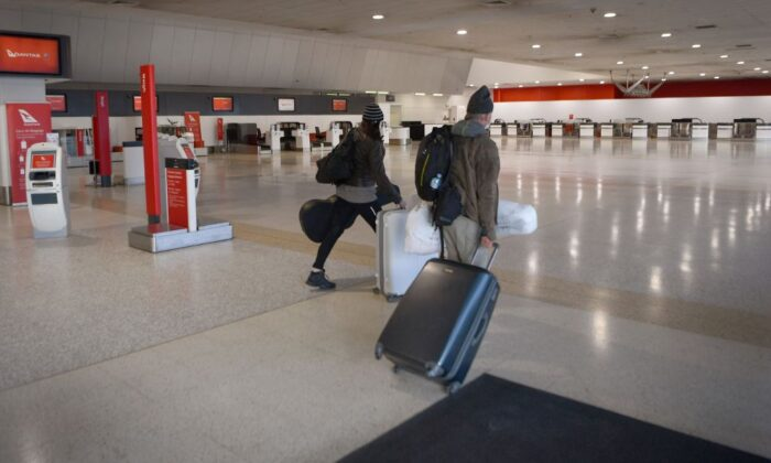Travellers walk through a deserted Qantas terminal at Melbourne Airport in Melbourne, Australia on Aug. 26, 2021 (William West/AFP via Getty Images)