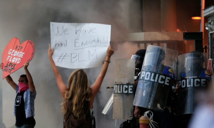 Police in riot gear face a protest outside a police station against the killing George Floyd on May 30, 2020, in Miami. (Cliff Hawkins/Getty Images)